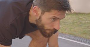 Retrato del primer del basculador masculino deportivo caucásico adulto que se prepara para correr en el estadio en la ciudad urba almacen de metraje de vídeo