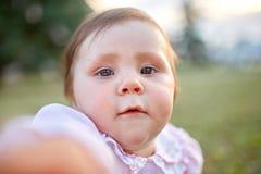Retrato del primer del bebé contra el prado verde que mira para arriba a la cámara al aire libre en luz del sol Foto de archivo