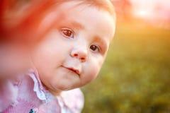 Retrato del primer del bebé contra el prado verde que mira para arriba a la cámara al aire libre en luz del sol Foto de archivo libre de regalías