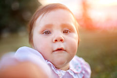 Retrato del primer del bebé contra el prado verde que mira para arriba a la cámara al aire libre en luz del sol Fotografía de archivo