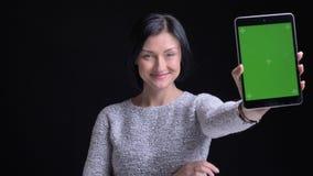 Retrato del primer del caucásico hermoso alegre adulto femenino usando la tableta y con confianza mostrar la pantalla verde a metrajes