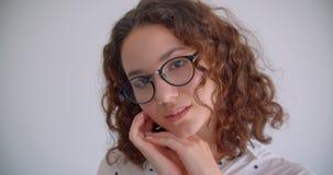 Retrato del primer del caucásico rizado de pelo largo atractivo joven femenino en los vidrios que sonríen atractivo mirando la cá almacen de video