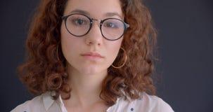 Retrato del primer del caucásico rizado de pelo largo bonito joven femenino en los vidrios que miran la cámara con el fondo almacen de metraje de vídeo