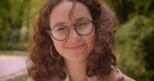 Retrato del primer del caucásico rizado de pelo largo bonito joven femenino en los vidrios que sonríen alegre mirando la cámara almacen de video