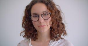 Retrato del primer del caucásico rizado de pelo largo lindo joven femenino en los vidrios que sonríen feliz mirando la cámara con metrajes