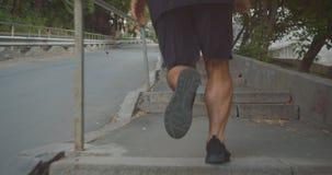 Retrato del primer del corredor masculino deportivo motivado del adulto que activa encima de las escaleras en la calle en la ciud almacen de video