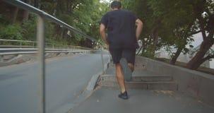 Retrato del primer del corredor masculino deportivo resuelto del adulto que activa encima de las escaleras en la calle en la ciud almacen de video