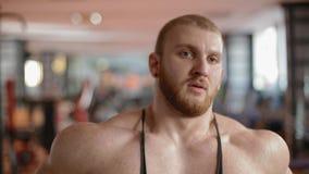 Retrato del primer del culturista en el gimnasio que respira profundamente almacen de video