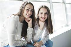 Retrato del primer de abrazar a 2 mujeres jovenes hermosas que se divierten Imágenes de archivo libres de regalías