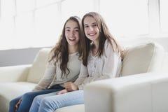 Retrato del primer de abrazar a 2 mujeres jovenes hermosas que se divierten en el sofá Foto de archivo libre de regalías