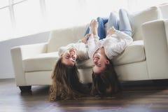 Retrato del primer de abrazar a 2 mujeres jovenes hermosas que se divierten en el sofá Imagen de archivo libre de regalías