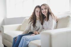 Retrato del primer de abrazar a 2 mujeres jovenes hermosas que se divierten en el sofá Fotografía de archivo libre de regalías