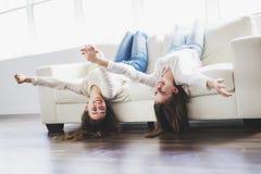 Retrato del primer de abrazar a 2 mujeres jovenes hermosas que se divierten en el sofá Imagen de archivo