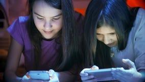 Retrato del primer de dos adolescentes con los teléfonos móviles en la noche Imagen de archivo libre de regalías