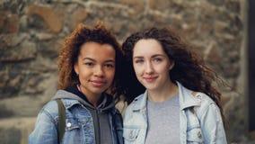 Retrato del primer de dos amigos de las mujeres bastante jovenes que se unen cerca de la pared de piedra, sonriendo y mirando la  metrajes