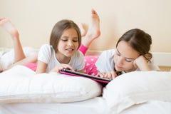 Retrato del primer de dos hermanas adolescentes que usan la tableta en cama Fotografía de archivo
