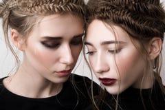 Retrato del primer de dos modelos de la belleza con las trenzas Imagen de archivo libre de regalías