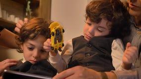 Retrato del primer de dos muchachos gemelos de pelo rizado árabes que miran atento en el juguete de la tenencia de la tableta almacen de video