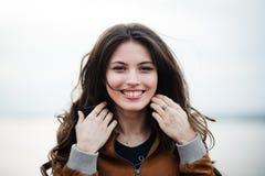 Retrato del primer de la capa de cuero que lleva de la mujer atractiva hermosa feliz joven que sonríe y que se coloca sobre luz Imágenes de archivo libres de regalías