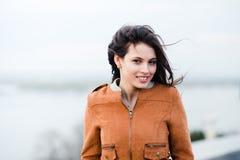 Retrato del primer de la capa de cuero que lleva de la mujer atractiva hermosa feliz joven que sonríe y que se coloca sobre luz Foto de archivo libre de regalías