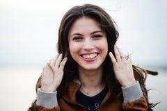 Retrato del primer de la capa de cuero que lleva de la mujer atractiva hermosa feliz joven que sonríe y que se coloca sobre luz Fotos de archivo