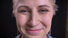 Retrato del primer de la cara femenina caucásica de mediana edad feliz que mira derecho la cámara y que sonríe amablemente metrajes
