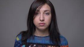 Retrato del primer de la cara femenina morena caucásica adulta que mira la cámara con el fondo aislado en gris almacen de video