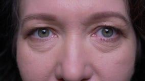 Retrato del primer de la cara femenina morena caucásica vieja con los ojos que miran la cámara con la expresión facial sonriente  metrajes