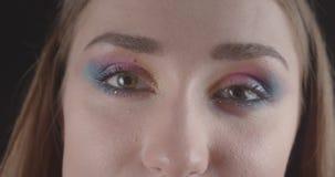 Retrato del primer de la cara femenina de pelo corto caucásica alegre joven con los ojos con maquillaje lindo del brillo con el f almacen de video