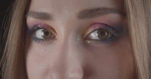 Retrato del primer de la cara femenina de pelo corto caucásica bonita joven con los ojos con el maquillaje del brillo que present almacen de video