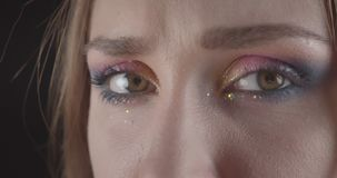 Retrato del primer de la cara femenina de pelo corto caucásica divertida joven con los ojos con maquillaje del brillo con el fond metrajes