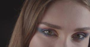 Retrato del primer de la cara femenina de pelo corto caucásica juguetona joven con los ojos con maquillaje lindo del brillo con e almacen de video