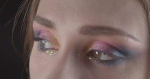 Retrato del primer de la cara femenina de pelo corto caucásica linda joven con los ojos con el maquillaje del brillo que presenta metrajes