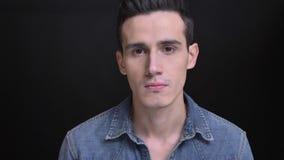 Retrato del primer de la cara masculina caucásica joven con los ojos marrones que miran derecho la cámara con el fondo aislado en almacen de video