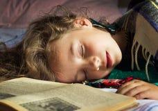 Retrato del primer de la colegiala rizada joven que duerme en los libros Imagen de archivo libre de regalías