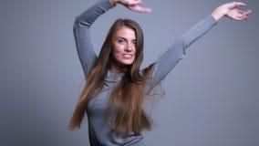 Retrato del primer de la diversión femenina caucásica joven feliz del baile y el tener con el fondo aislado en gris metrajes