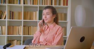 Retrato del primer de la empresaria atractiva joven que habla feliz en el teléfono que se sienta delante del ordenador portátil e metrajes