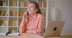 Retrato del primer de la empresaria atractiva joven que habla ocasional en el teléfono que se sienta delante del ordenador portát almacen de video