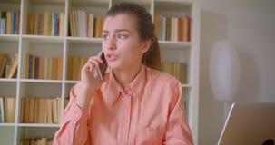 Retrato del primer de la empresaria atractiva joven que tiene una llamada de teléfono que trabaja en el ordenador portátil en la  almacen de metraje de vídeo