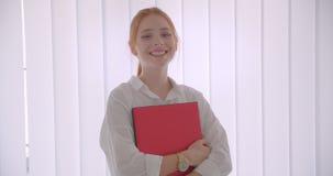 Retrato del primer de la empresaria caucásica bonita joven del pelirrojo que sostiene el ordenador portátil que sonríe feliz mira almacen de metraje de vídeo