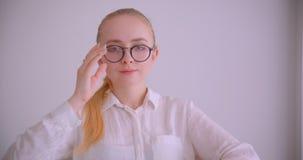 Retrato del primer de la empresaria rubia caucásica bonita joven en vidrios que sonríe alegre mirando sentarse de la cámara almacen de metraje de vídeo