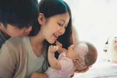 Retrato del primer de la familia feliz con el pequeño bebé en el dormitorio imágenes de archivo libres de regalías