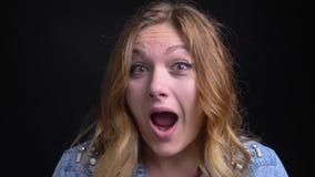 Retrato del primer de la hembra caucásica adulta con el pelo rubio corto que hace diversas expresiones faciales y que juega a un  metrajes