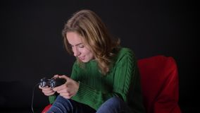 Retrato del primer de la hembra caucásica adulta que juega a los videojuegos con el entusiasmo dentro almacen de video