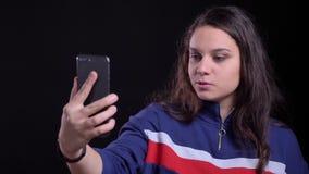 Retrato del primer de la hembra caucásica atractiva adulta que tiene una conversación vía la llamada video en el teléfono con el  almacen de metraje de vídeo