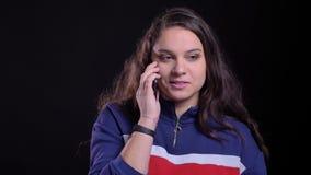 Retrato del primer de la hembra caucásica atractiva adulta que tiene una llamada de teléfono con el fondo aislado en negro metrajes