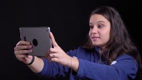 Retrato del primer de la hembra caucásica atractiva adulta que tiene una llamada video en la tableta con el fondo aislado encendi metrajes