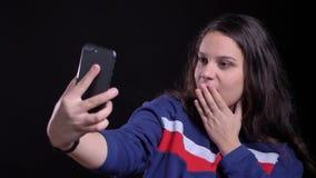 Retrato del primer de la hembra caucásica atractiva adulta que toma selfies en el teléfono y que presenta delante de la cámara co almacen de metraje de vídeo
