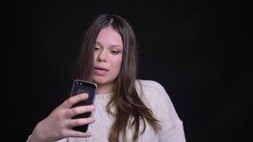 Retrato del primer de la hembra caucásica atractiva joven que tiene una conversación casual vía la llamada video en el teléfono metrajes