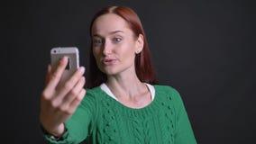 Retrato del primer de la hembra caucásica atractiva que tiene una llamada video en el teléfono en un humor positivo almacen de video